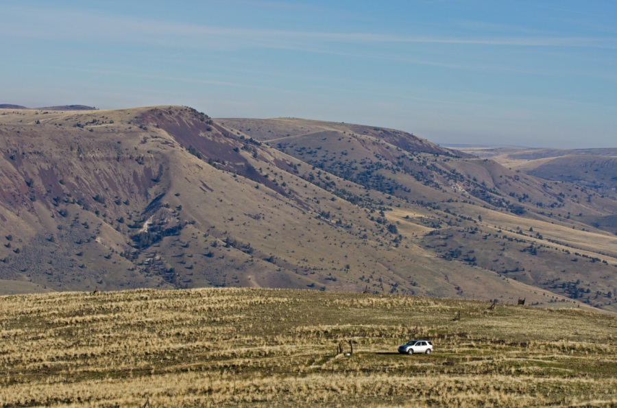 The SUV looks small in the wide expanse of the ranchland