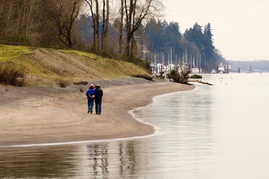A couple walking the sandy beach near the end of Sauvie Island