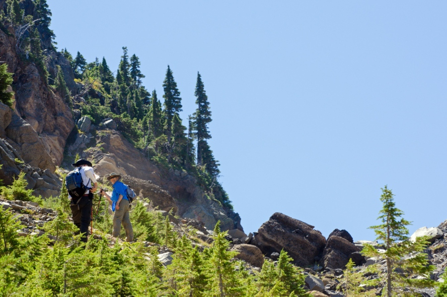 Hikers climbing the steep glacial moraine below Three Fingered Jack