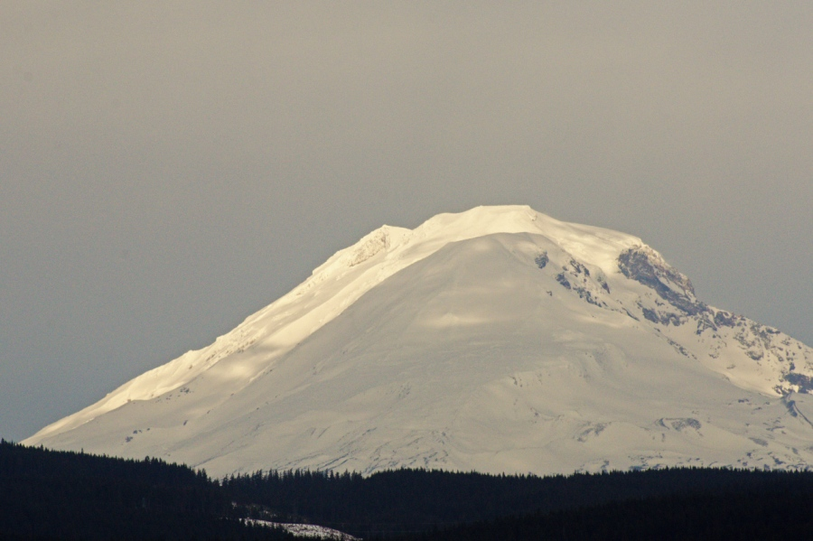 Sunshine highlighting fresh snow on the summit of Mt. Adams