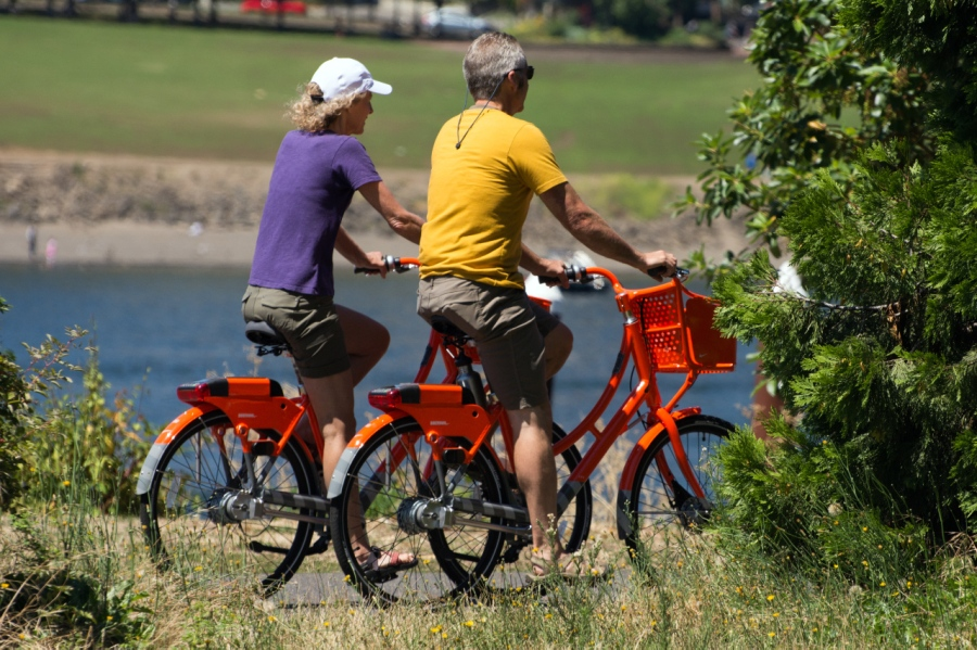 Folks enjoying the nice weather on low-cost Rideshare bicycles